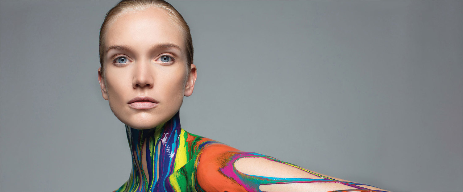 A woman covered in coloured paint looks to the camera