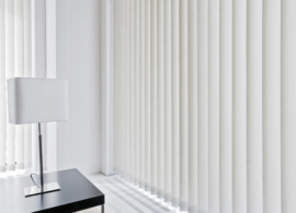 Large window with Russells Vertical blinds next to coffee table and lamp