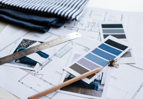 House plans, paint samples, ruler and pencil laid on a table
