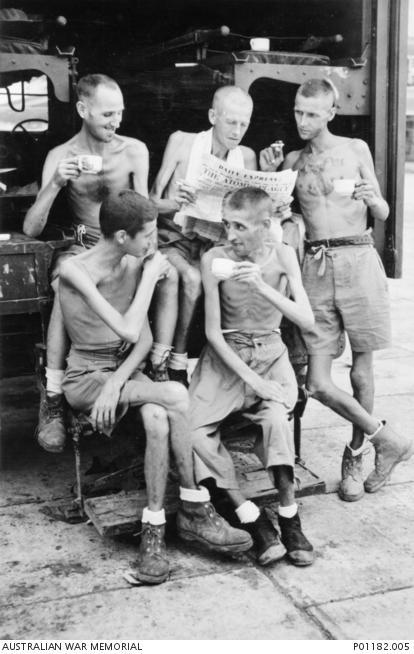 Five Australian former POWs relax with cups of tea and a newspaper after the Japanese surrender. Their thin bodies show the physical effects of captivity. (Courtesy of the Australian War Memorial