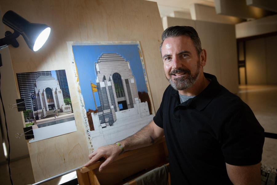 Facing the camera, his painting of the Memorial rests on the easel behind him.