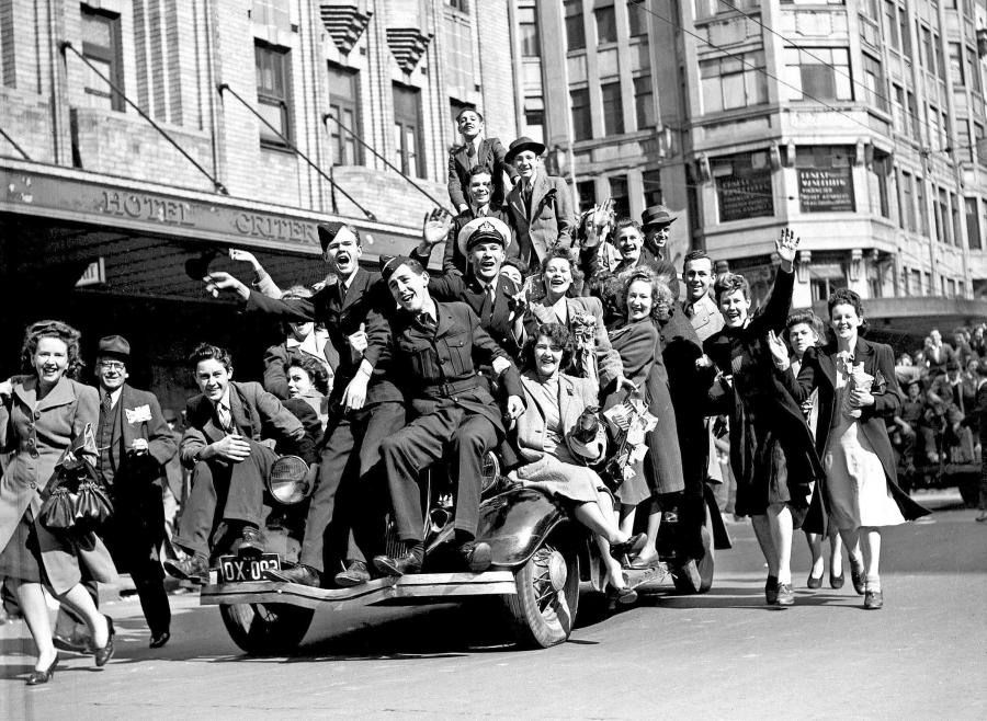 Two airmen and a merchant naval officer join civilian revellers and pile on to a car in Sydney to celebrate the announcement of Japan's surrender in August 1945. Courtesy of the Sydney Morning Herald