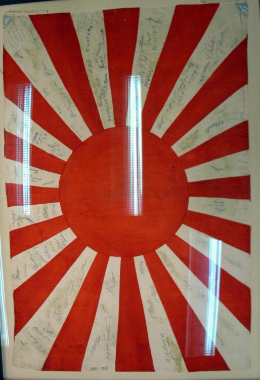 This Japanese flag was taken from the ruins of the Japanese naval arsenal at Hiro by Private Ray Hore and his mates from the 66th Battalion, BCOF. The flag is signed by the men of A Company and a few RAAF personnel.