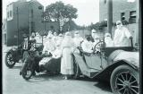 A group of nurses and doctors dressed in surgical whites and masks about to get on motorbikes and cars to tend influenza patients
