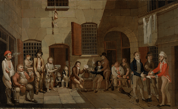 A group of ragged men and children sit around, legs shackled, in a dreary stone structure.