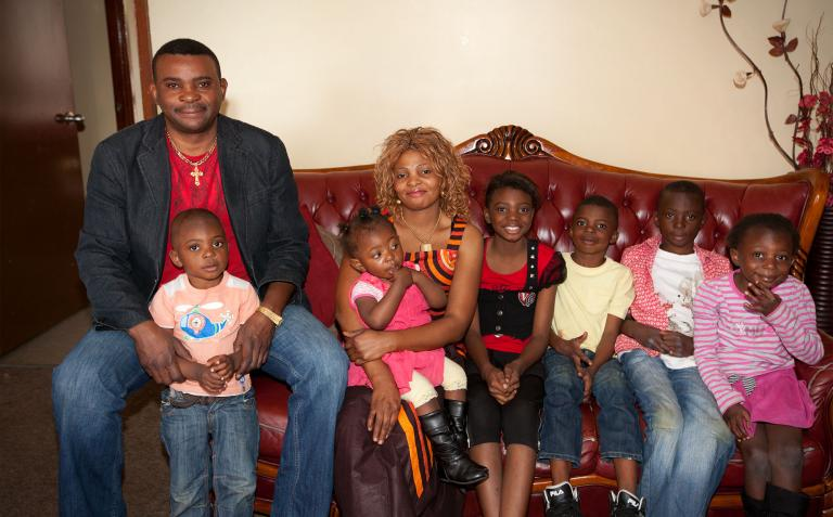 Justine and her family sitting on a couch.