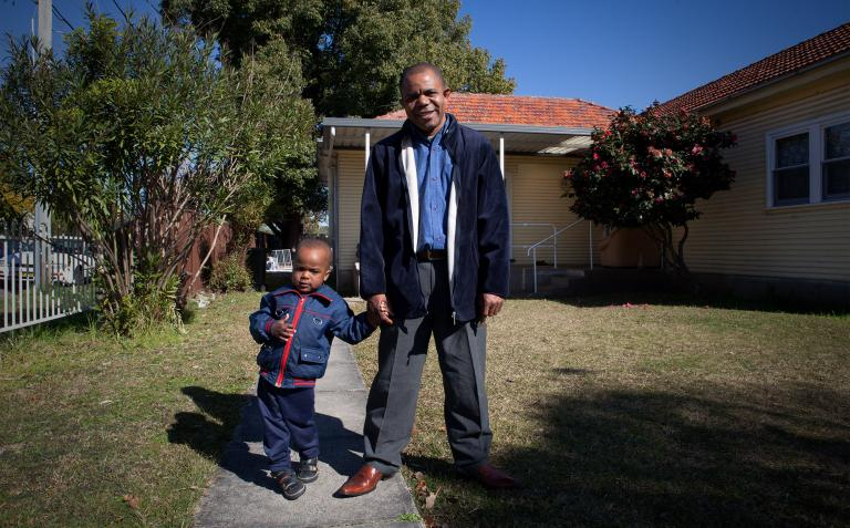Image of Theophile and his son in front of their house.