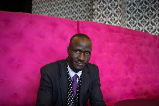 Deng sitting with a pink backdrop.