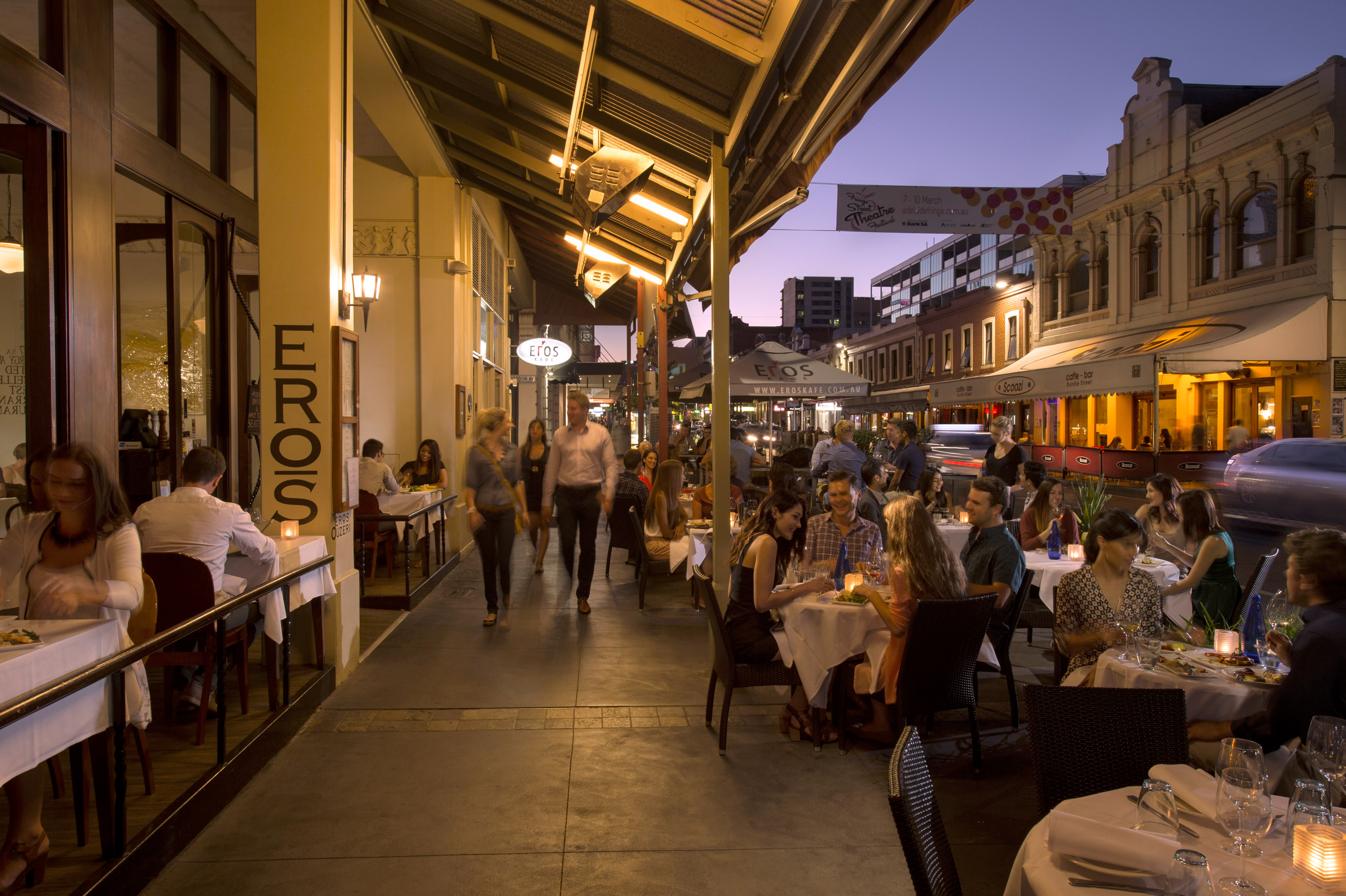 People dining at outdoor tables in Adelaide.