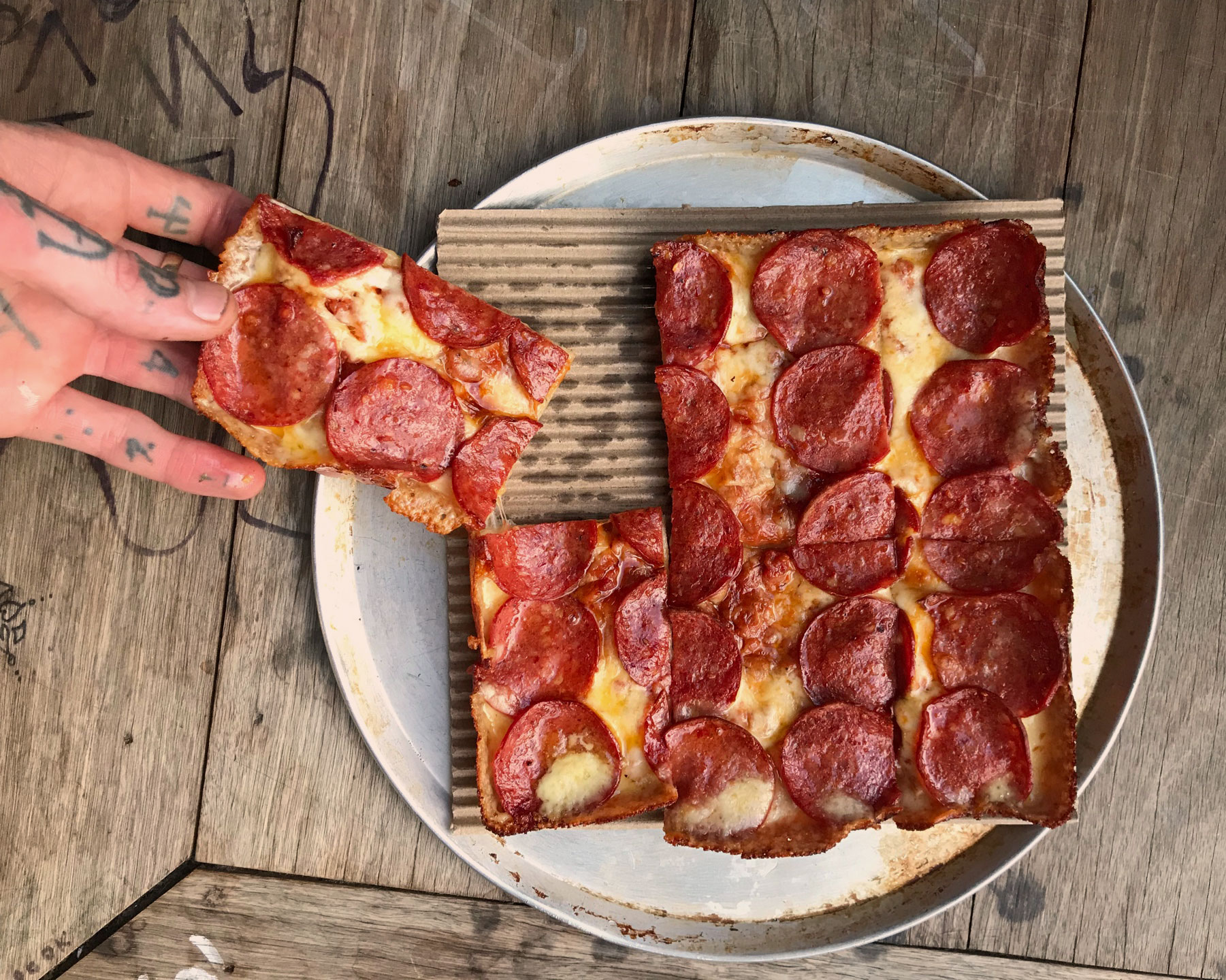 Mary's Detroit style pizza. A square pizza with pepperoni. A hand is pulling a slice away from the plate.