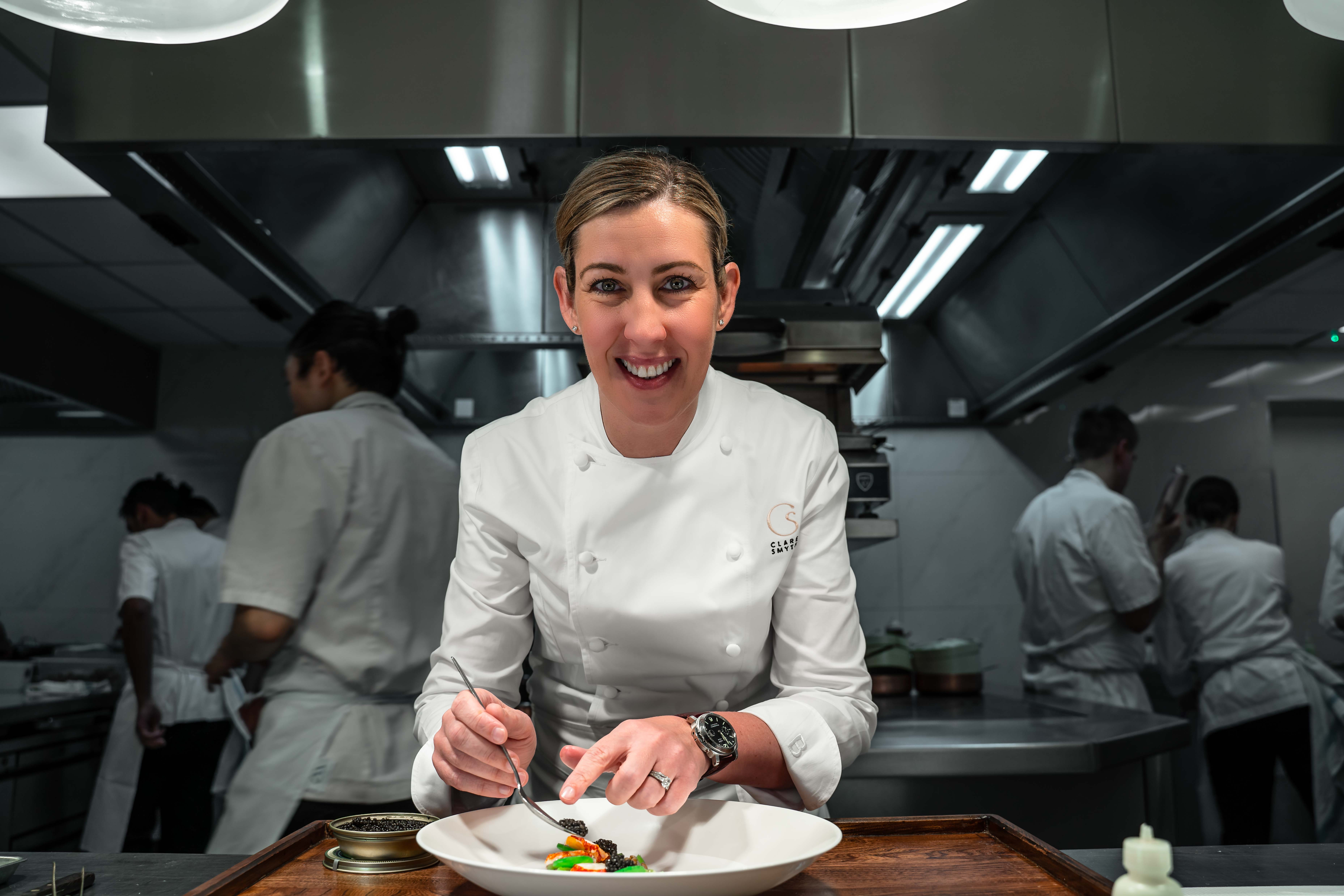 Clare Smyth plating up at a kitchen pass.