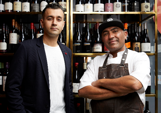 Dheeraj Bhatia and Jessi Singh looking into camera, standing in front of wine-filled shelves.