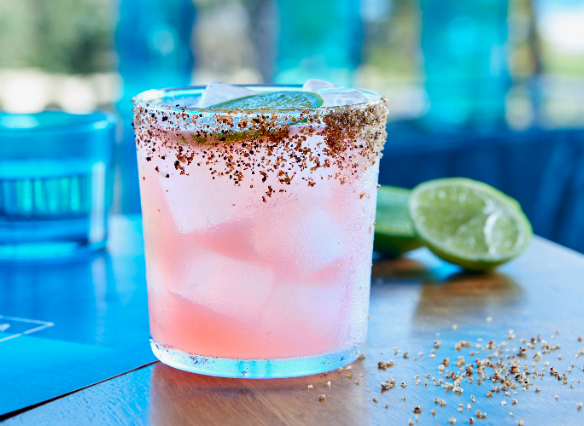 Pale pink margarita in an old fashioned glass with chilli and salt rim against a blue background