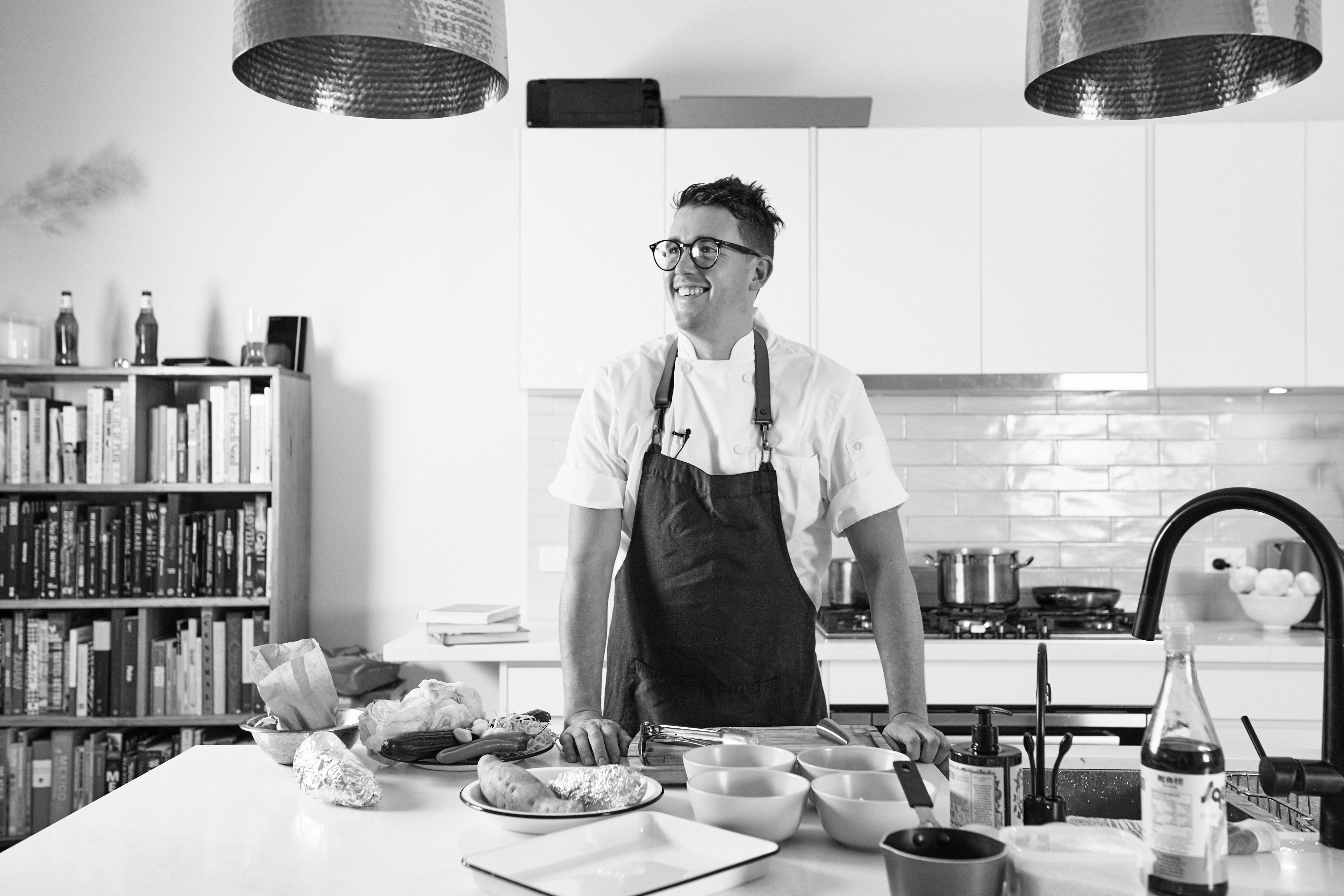 Black and white image of Chef Charlie Carrington looking away from camera and smiling in home kitchen